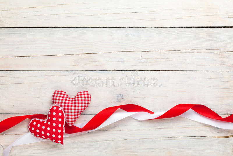 De achtergrond van de valentijnskaartendag met stuk speelgoed harten en linten stock afbeeldingen