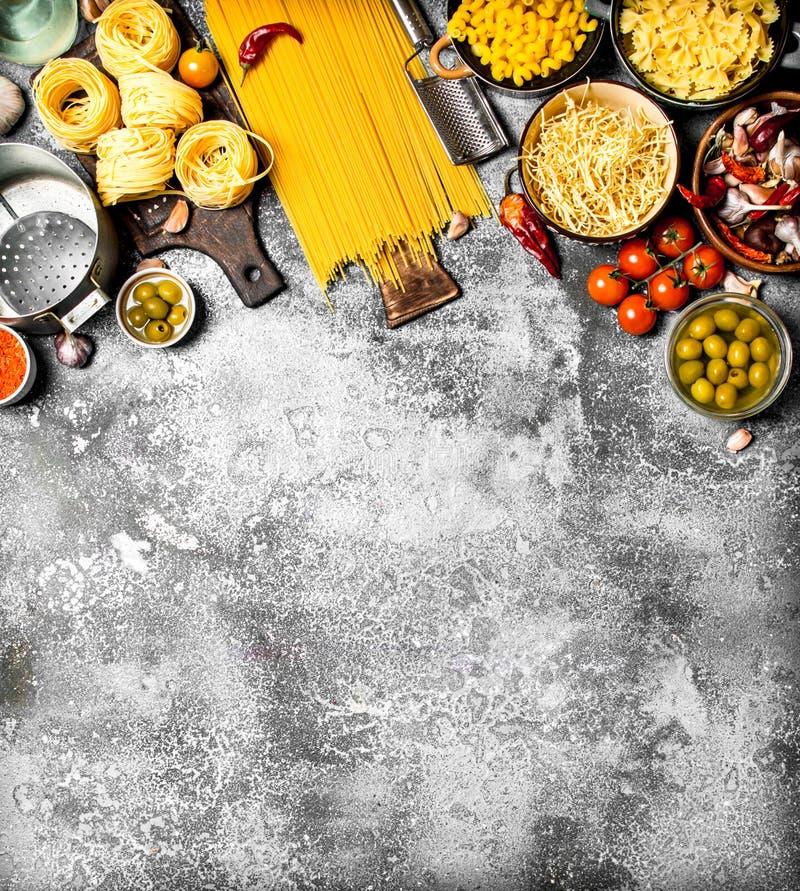 De achtergrond van deegwaren Diverse deegwaren met groenten en kruiden stock afbeeldingen