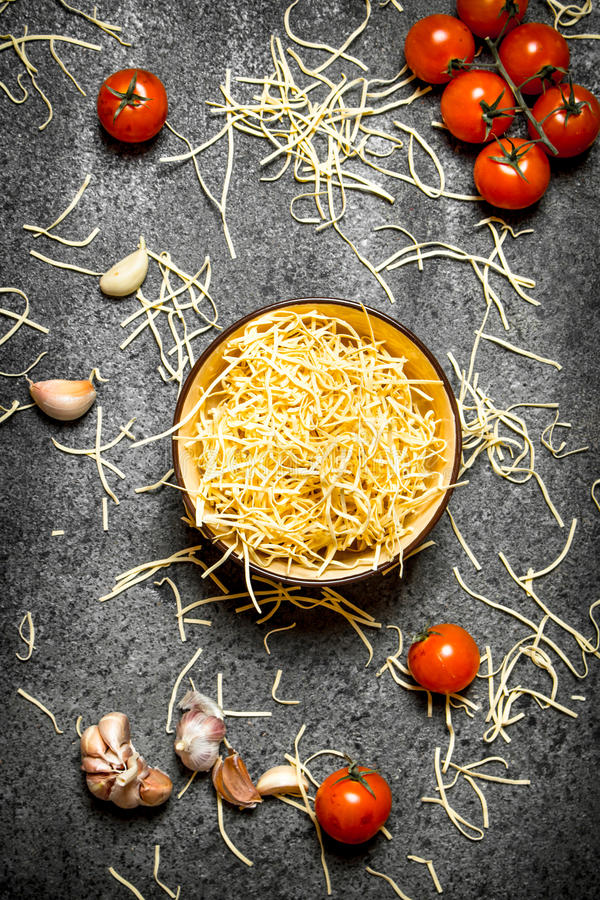 De achtergrond van deegwaren Noedels met tomaten en knoflook stock afbeelding