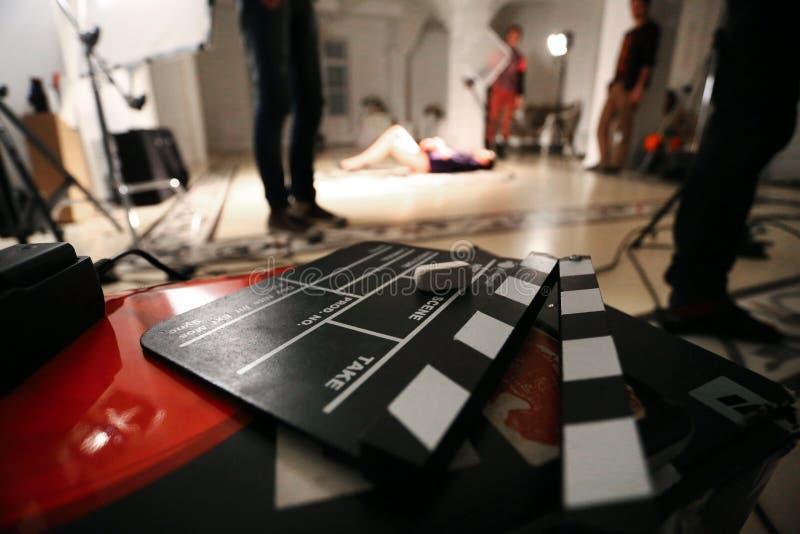 De Achtergrond van de filmfilm, clapperboard en videolicht in een studio stock foto's