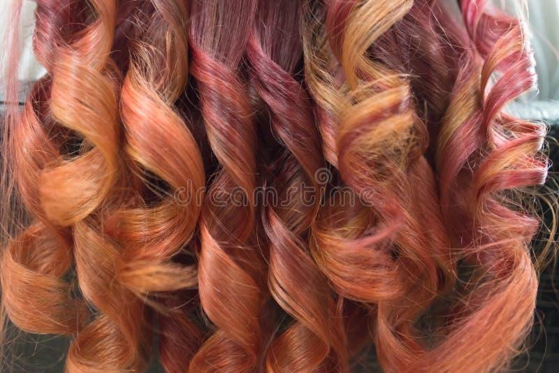 De achtergrond van heldere gekrulde sloten van lang haar met schittert van karmozijnrood aan rood stock foto's