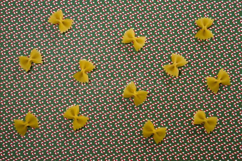De achtergrond van het deegwarenpatroon Droog volkorenmeel farfalle op Kerstmisgrond Vlak leg Hoogste mening stock afbeeldingen