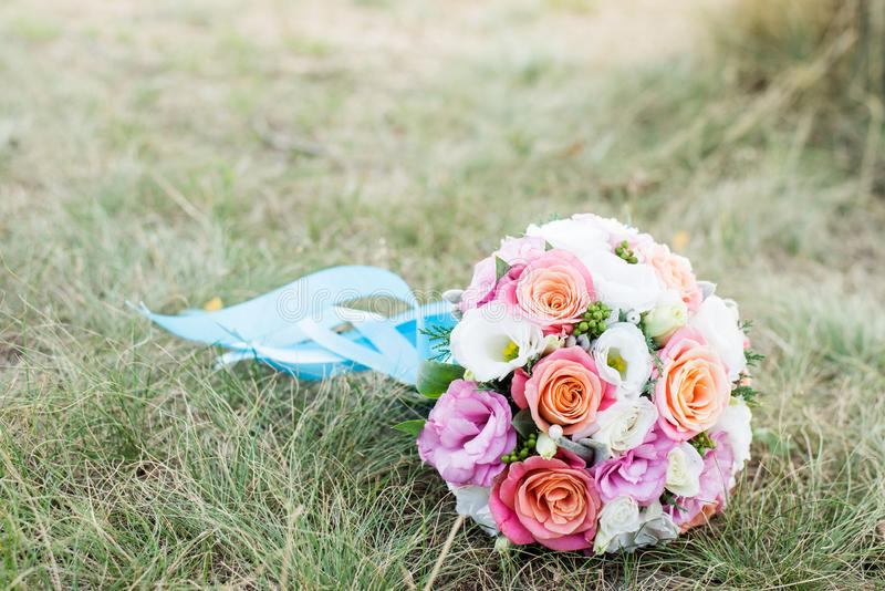 De achtergrond van het huwelijk Het boeket van de bruid met roze en witte bloemen op het gras Verklaring van liefde Huwelijkskaar stock foto