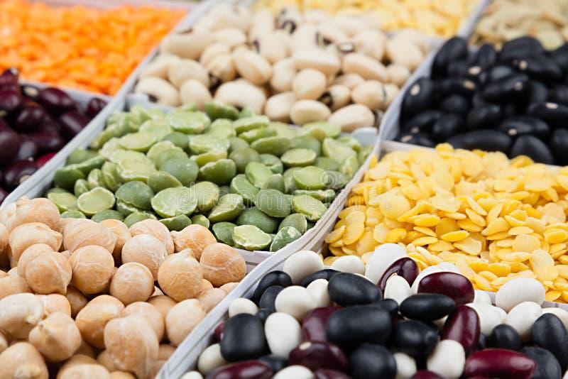 De achtergrond van het impulsenvoedsel, assortiment - peulvrucht, nierbonen, erwten, linzen in vierkante cellenmacro royalty-vrije stock afbeelding
