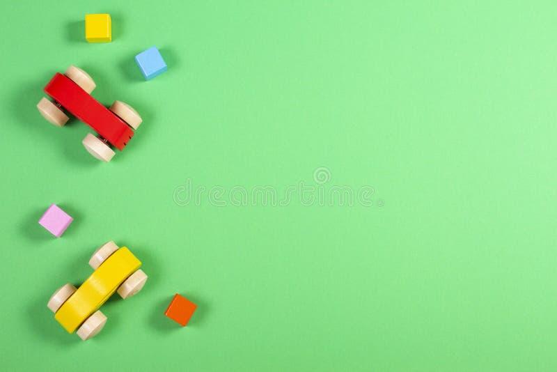 De achtergrond van het jong geitjespeelgoed Kleurrijke houten auto's en kubussen op groene kleurenachtergrond royalty-vrije stock foto
