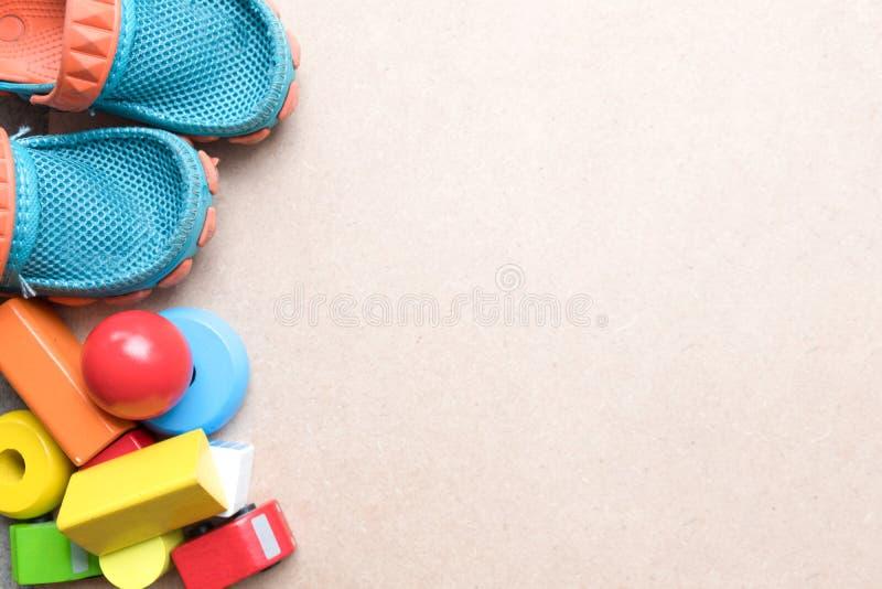 De achtergrond van het jonge geitjesspeelgoed met babyschoenen en houten blokken stock afbeelding