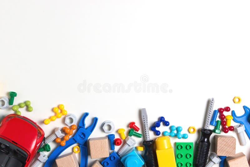 De achtergrond van het jonge geitjesspeelgoed met kleurrijke stuk speelgoed hulpmiddelen, bouten, noten, auto, bouwblokken, kubee royalty-vrije stock foto's