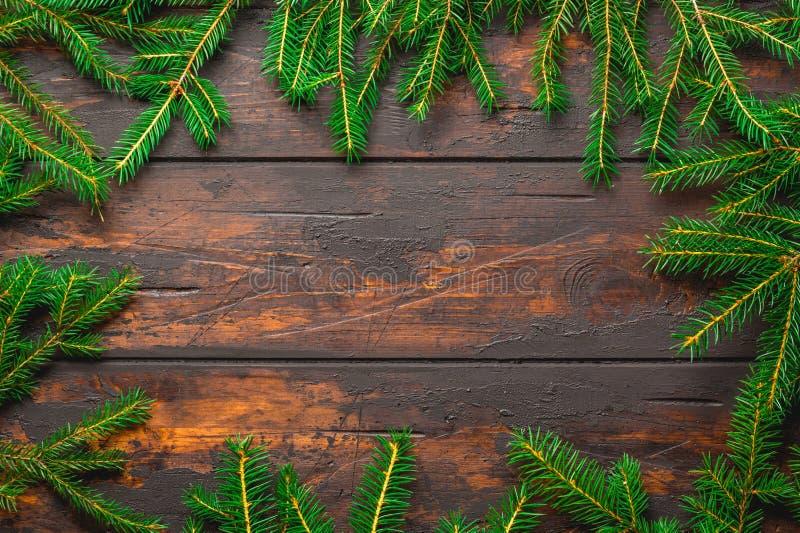 De achtergrond van het Kerstmiskader De takken van de Kerstmisspar op bruine rustieke houten raad met exemplaarruimte royalty-vrije stock afbeeldingen
