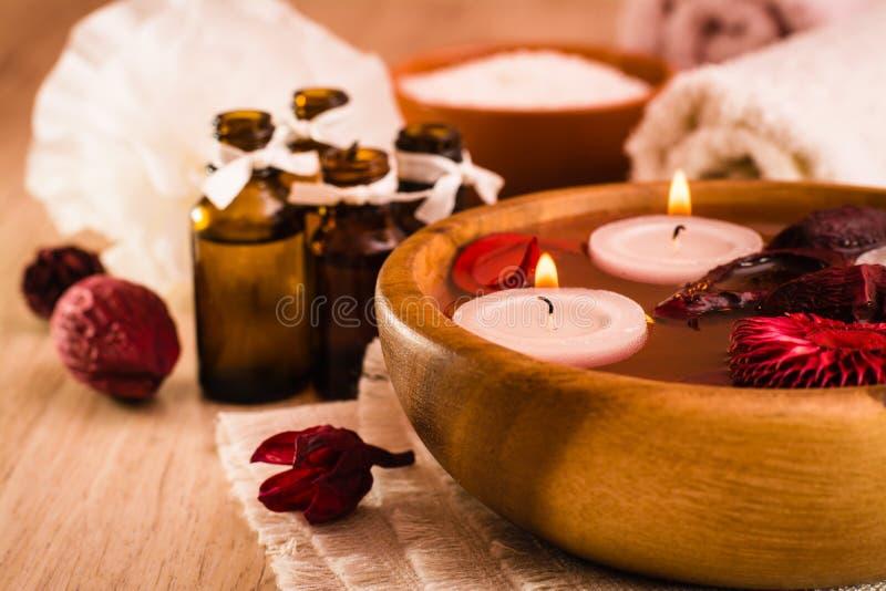 De achtergrond van het kuuroord Aromatherapy, kuuroordpunten, kaarsen, etherische oliën, overzees zout, handdoeken en bloemen stock foto's