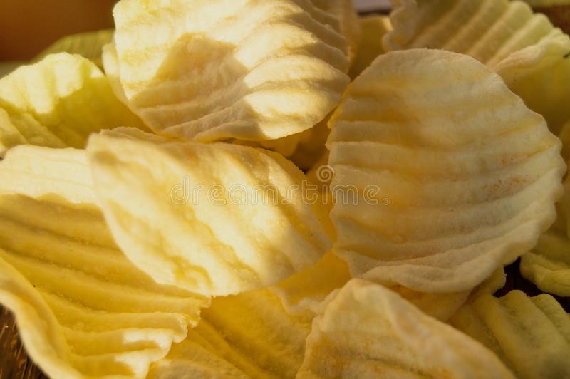 De achtergrond van het voedsel, smakelijke knapperige heerlijke zoute chips in de vorm van een zeeschelp met golven royalty-vrije stock afbeeldingen