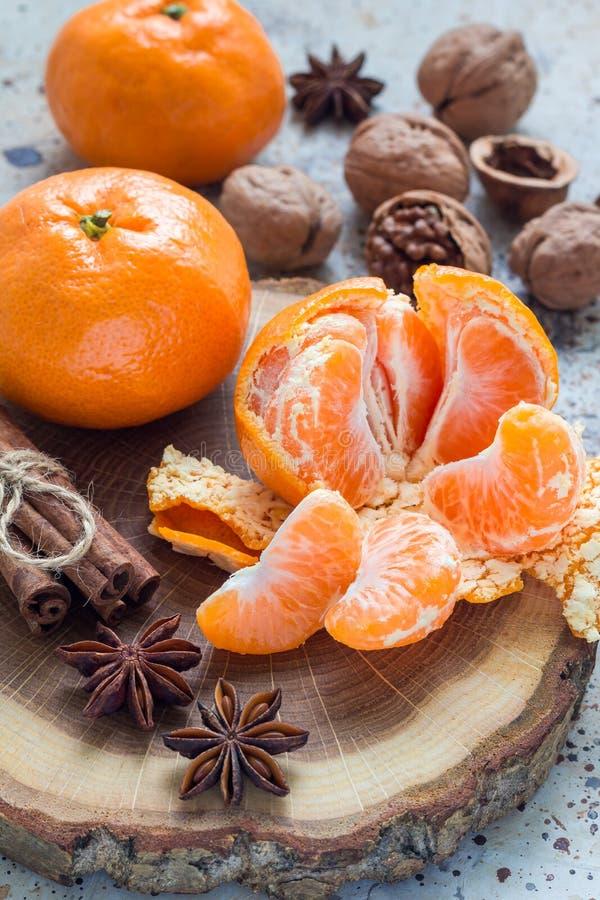 De achtergrond van Kerstmis Aromatische de winterkruiden, okkernoten en mandarins die op houten verticaal logboek leggen, royalty-vrije stock foto