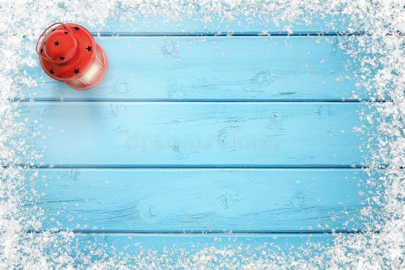De achtergrond van Kerstmis Blauwe bevroren houten lijst met sneeuwsneeuwvlokken op randen Rode lantaarn op linkerkant royalty-vrije stock afbeeldingen