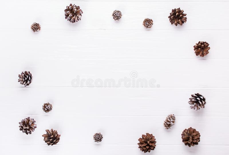 De achtergrond van Kerstmis Decoratie van Kerstmis de kader gemaakte denneappels rustieke elementen op witte trable stock afbeelding