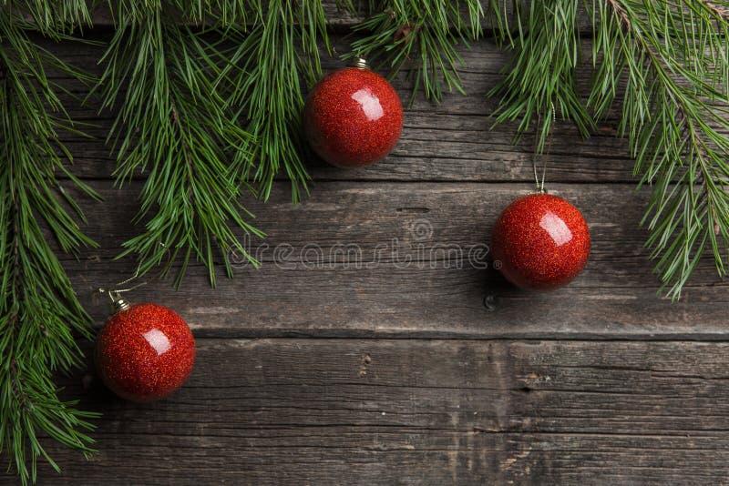 De achtergrond van Kerstmis Decoratie van de Kerstmisbal van de sparrentak de rode bij houten lijst stock foto