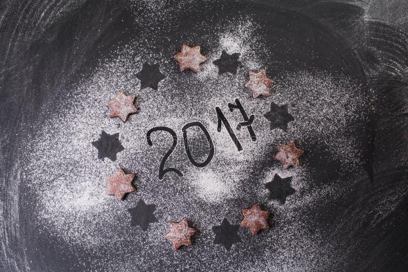 De achtergrond van Kerstmis 2017 geschreven met bloem en koekjessterren royalty-vrije stock afbeeldingen