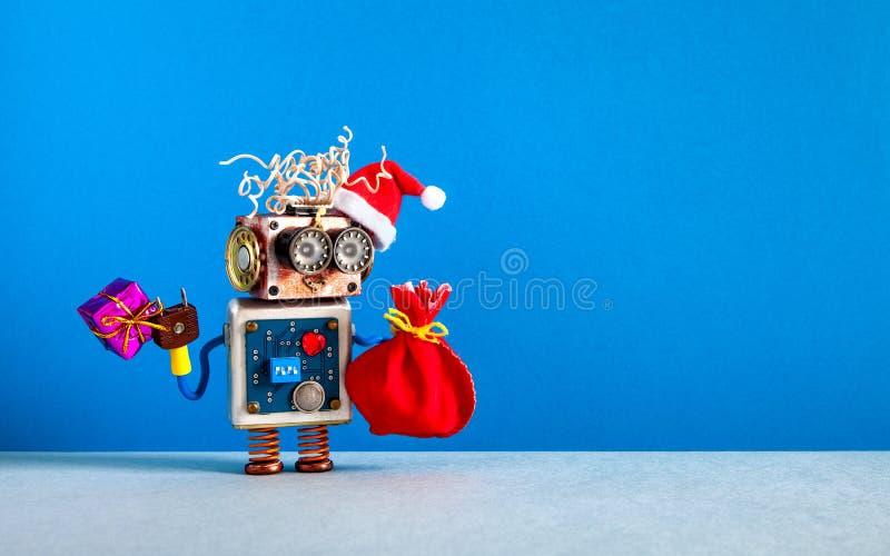 De achtergrond van Kerstmis De grappige robot van de Kerstmanhoed, houdt doosheden en een rode zak van giften Futuristisch Kerstm royalty-vrije stock afbeelding