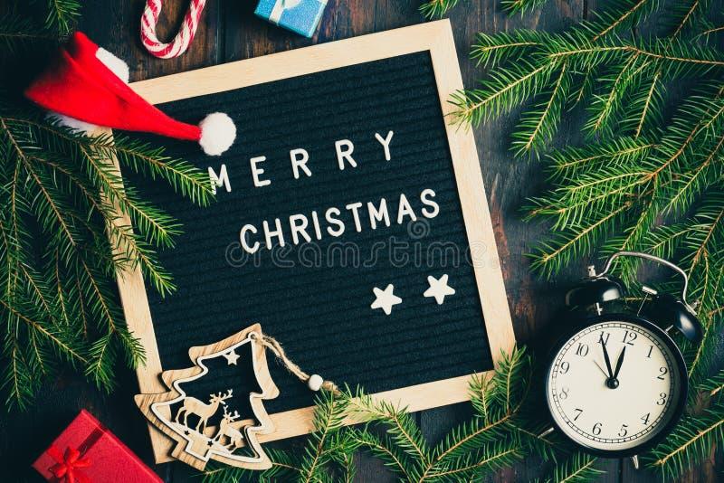 De achtergrond van Kerstmis De Kerstmisspar vertakt zich met uitstekende wekker en giftboxes op rustieke houten raad dichtbij bri royalty-vrije stock foto's
