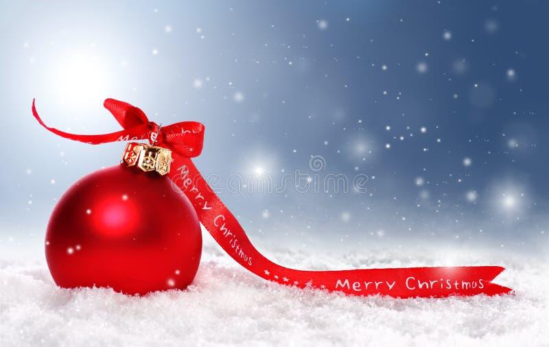 De achtergrond van Kerstmis met snuisterij, sneeuw en stock foto's