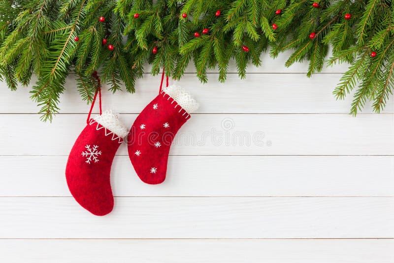 De achtergrond van Kerstmis Rode Kerstmissokken op witte houten achtergrond met Kerstmisspar De ruimte van het exemplaar stock afbeeldingen