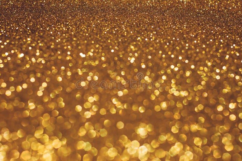 De achtergrond van de Kerstmisvakantie bokeh met gouden lichten Schitter gouden bokehachtergrond stock foto's
