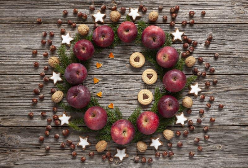 De achtergrond van de Kerstmisvakantie met eigengemaakte koekjes, rode appelen, royalty-vrije stock afbeeldingen