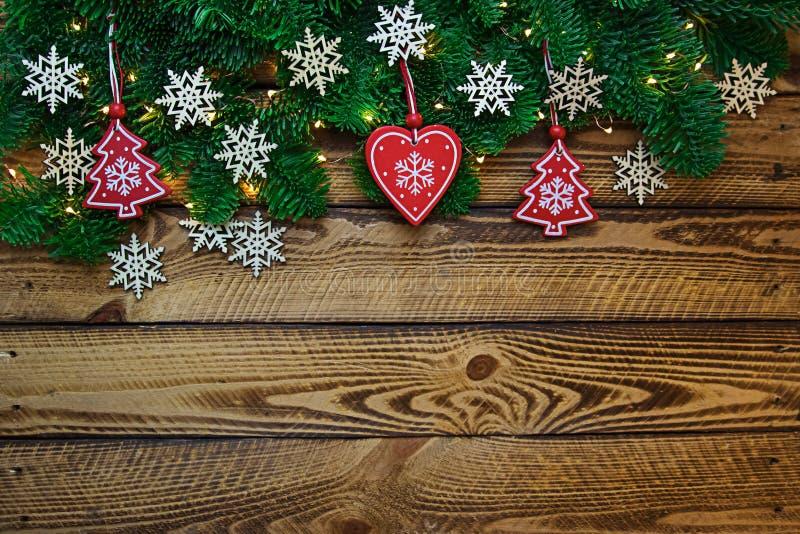 De achtergrond van de Kerstmisvakantie met sparrentakken en snowflokes over houten planken stock afbeelding