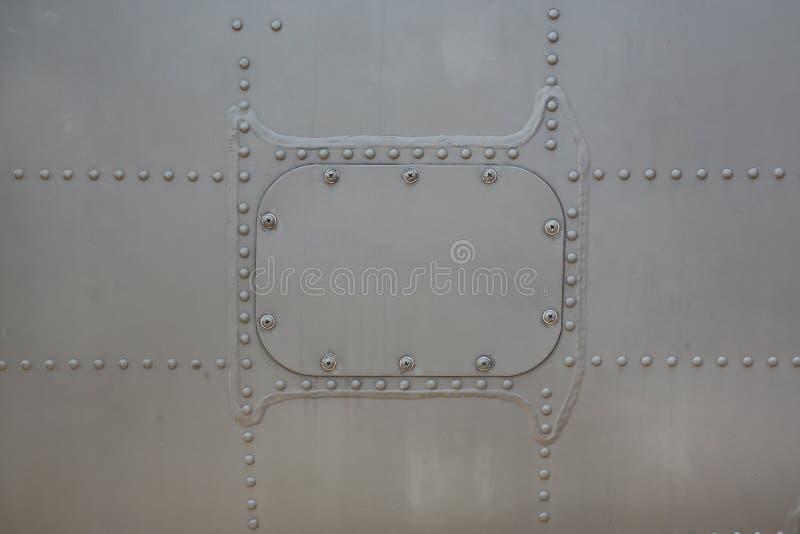 De achtergrond van de metaaloppervlakte van militaire vliegtuigen met dekking stock afbeeldingen