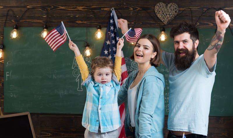 De achtergrond van de onafhankelijkheid Day De gelukkige familie viert Onafhankelijkheidsdag met Amerikaanse vlaggen in schoolkla stock afbeeldingen