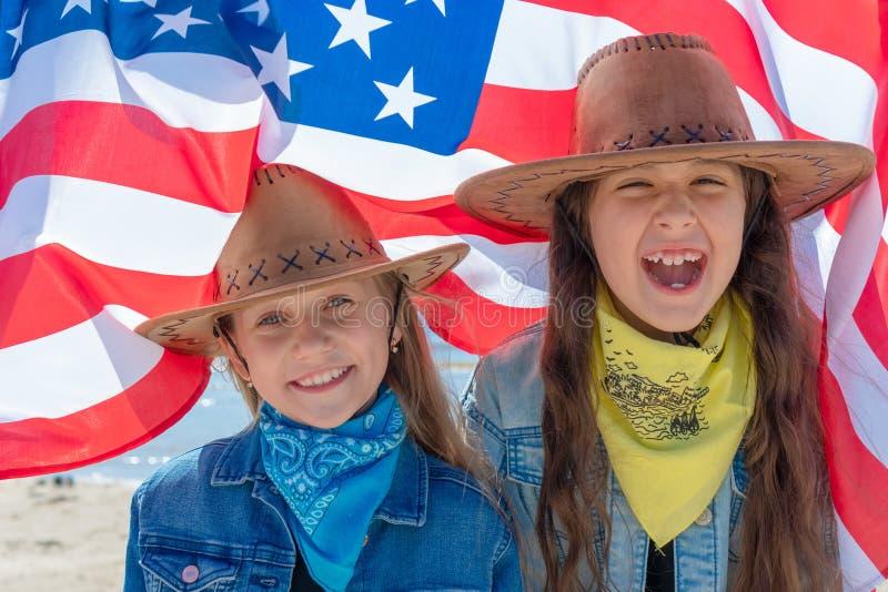 De achtergrond van de onafhankelijkheid Day Gelukkige jonge geitjes, leuke twee meisjes met Amerikaanse vlag De V.S. vieren 4 van stock foto's