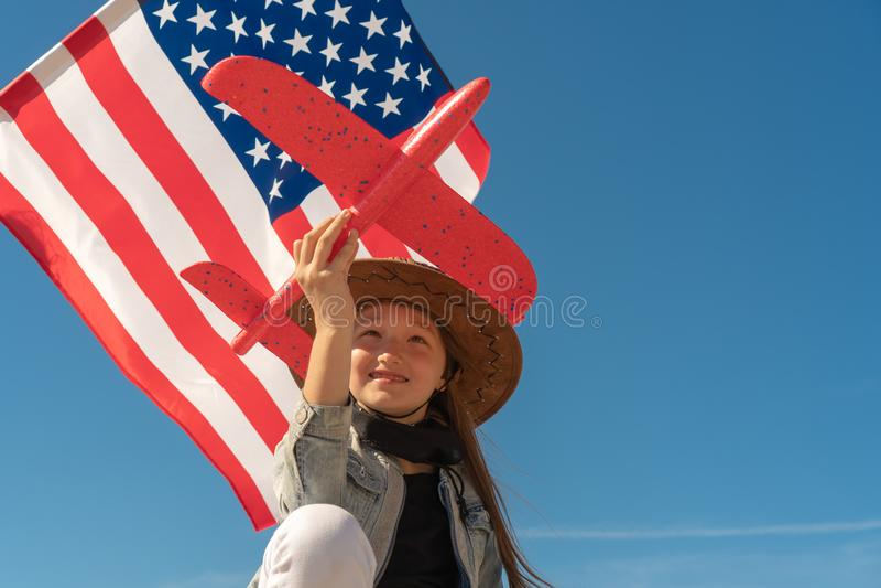 De achtergrond van de onafhankelijkheid Day Het mooie meisje in een cowboyhoed op de achtergrond van de Amerikaanse vlag houdt ee stock afbeelding