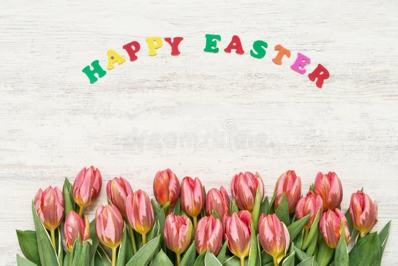 De achtergrond van Pasen Kleurrijke brieven die woorden GELUKKIGE PASEN en rode tulpen op witte achtergrond vormen exemplaar ruim royalty-vrije stock afbeeldingen