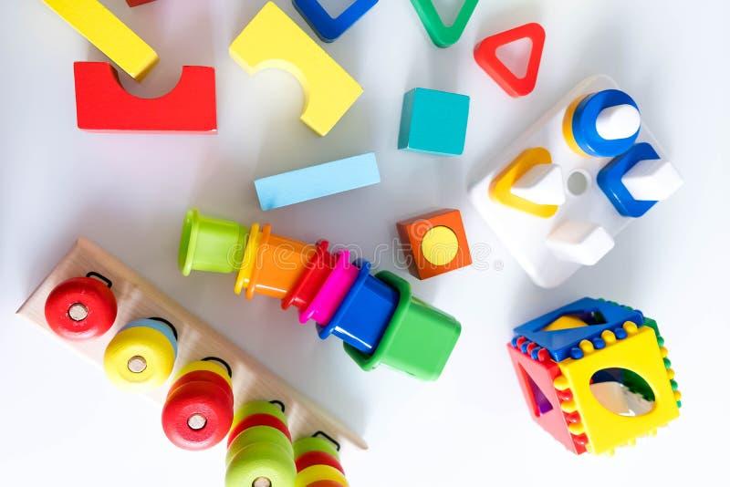 De achtergrond van speelgoedjonge geitjes Houten kubussen met aantallen en kleurrijke stuk speelgoed bakstenen op een witte achte stock afbeelding