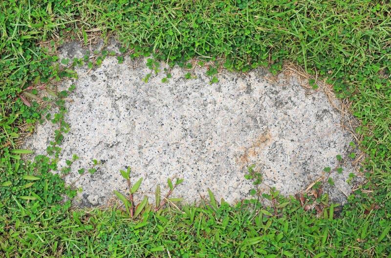 De achtergrond van de steentextuur met groen rond gras wordt behandeld dat Concreet patroon met exemplaarruimte op centrum stock fotografie