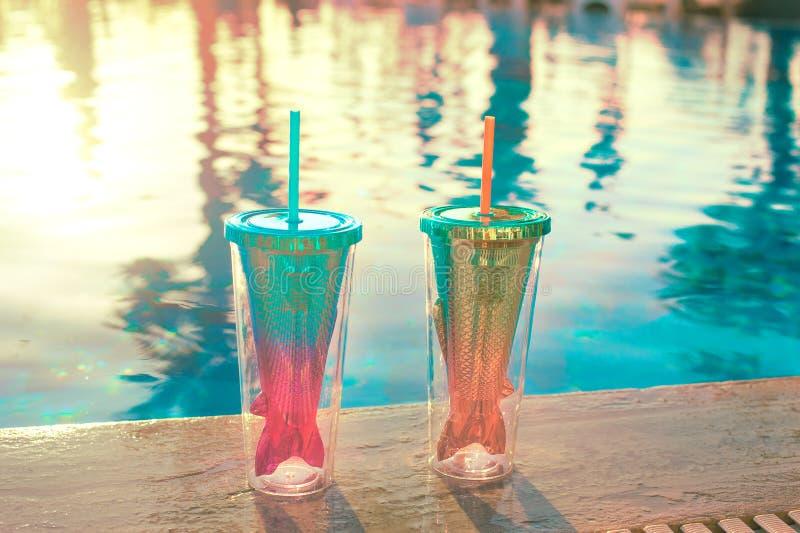 De achtergrond van de strandvakantie met twee cocktails in het glas dichtbij zwembad van de meerminstaart in luxueus hotel royalty-vrije stock afbeeldingen