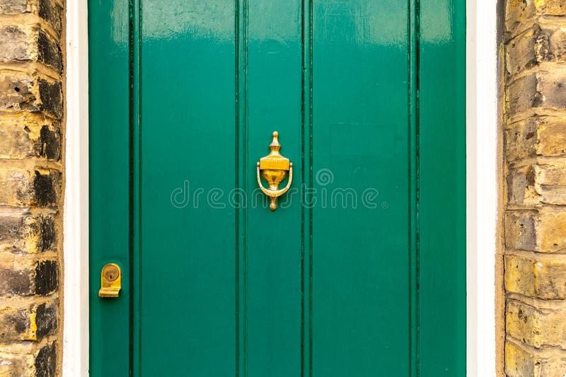De achtergrond van uitstekende groene geschilderde die deur en kloppersvignet kijkt van ouderwets uitstekend messingsmetaal wordt royalty-vrije stock foto's