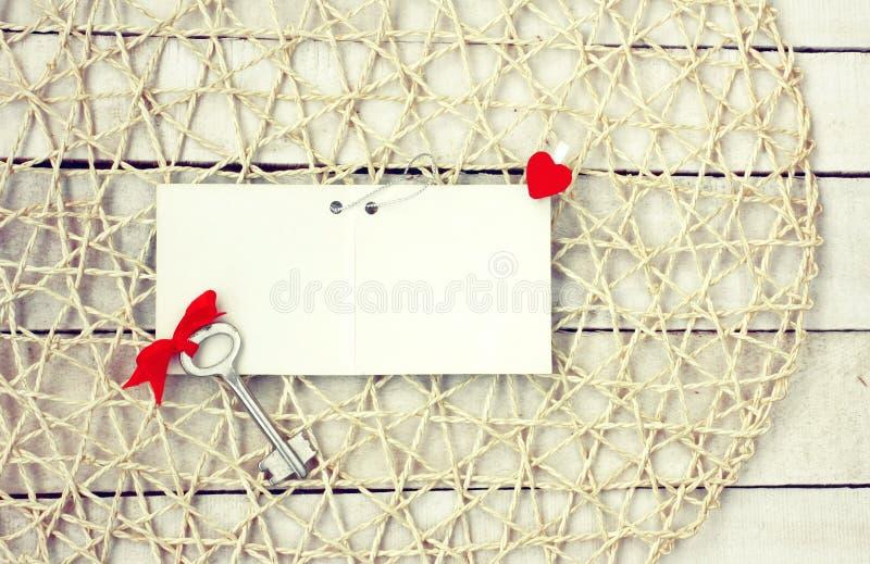 De achtergrond van de valentijnskaartendag, lege document markering, sleutel met rode boog en stock foto