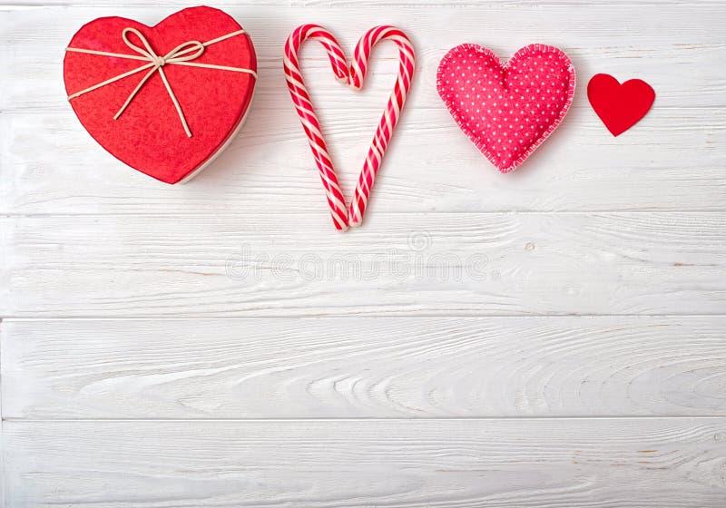 De achtergrond van de valentijnskaartendag met een samenstelling van valentijnskaart Suikergoed, prentbriefkaar, gift en stuk spe royalty-vrije stock foto