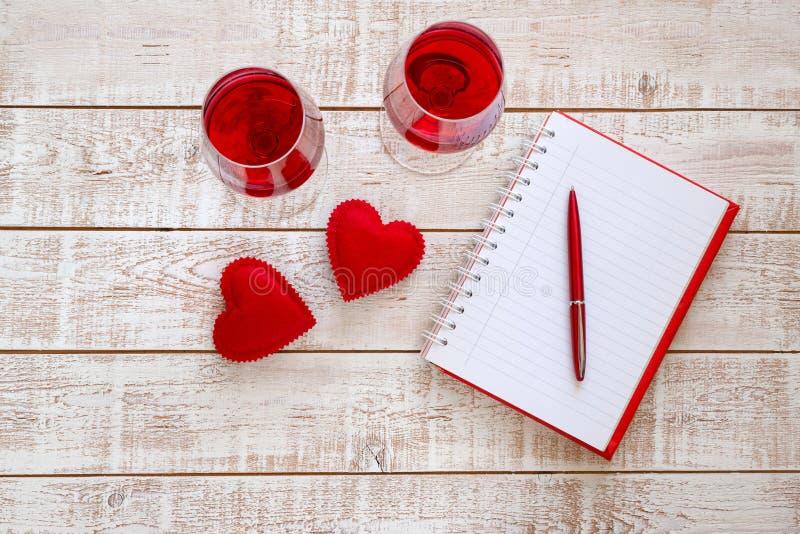 De achtergrond van de valentijnskaartendag met harten en glazen wijn over witte houten lijst royalty-vrije stock foto