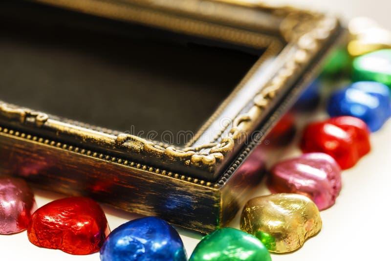 De achtergrond van de valentijnskaartendag met de kleurrijke vorm van het chocoladehart en gouden kader De ruimte van het exempla royalty-vrije stock afbeelding