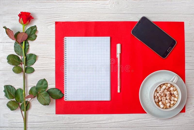 De achtergrond van de valentijnskaartendag met rood nam en een leeg notitieboekje voor romantische ingangen toe stock fotografie