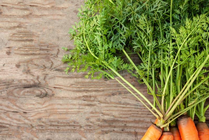 De achtergrond van verse oranje zoete wortel met groene bladeren in een stapel ligt op een houten oppervlakte royalty-vrije stock afbeeldingen