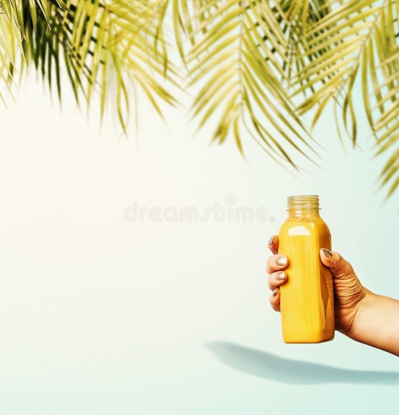De achtergrond van de zomerdranken met tropische palmbladen en gele drankfles in vrouwelijke hand bij pastelkleur blauwe achtergr stock afbeeldingen