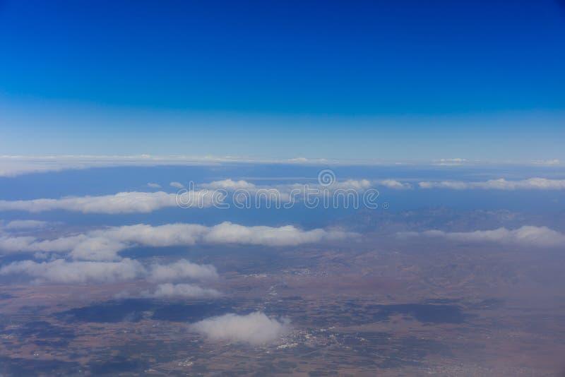 De achtergrond is volledig met sterren Blauwe hemel, witte wolken, land Mening van hierboven stock foto