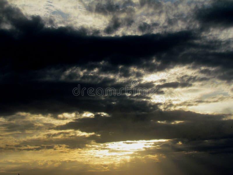 De achtergrondafbeelding van de spel capricieuze wolken van wolken en het licht van de zonsondergang bij zonsondergang stock afbeelding
