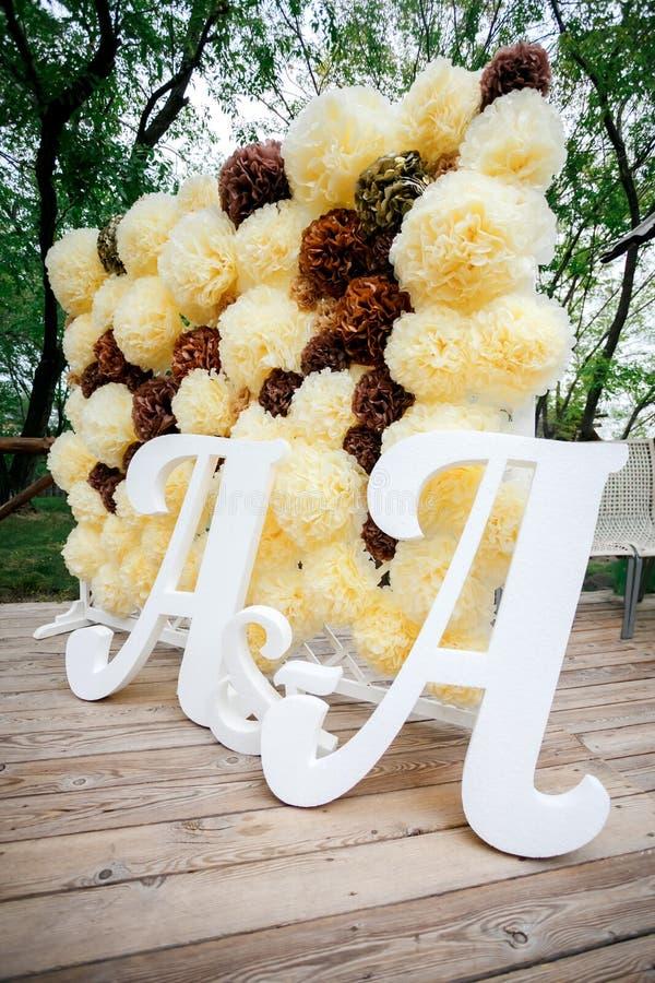 De achtergrondmuur van de bloempompon, de streek van de huwelijksdecoratie met dubbele brieven a Gele witte en bruine kleur stock afbeelding