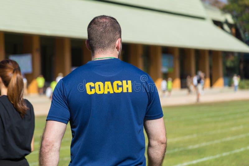 De achterkant van een mannelijke atletenbus in diepe blauwe t-shirt met schreeuwt royalty-vrije stock foto's