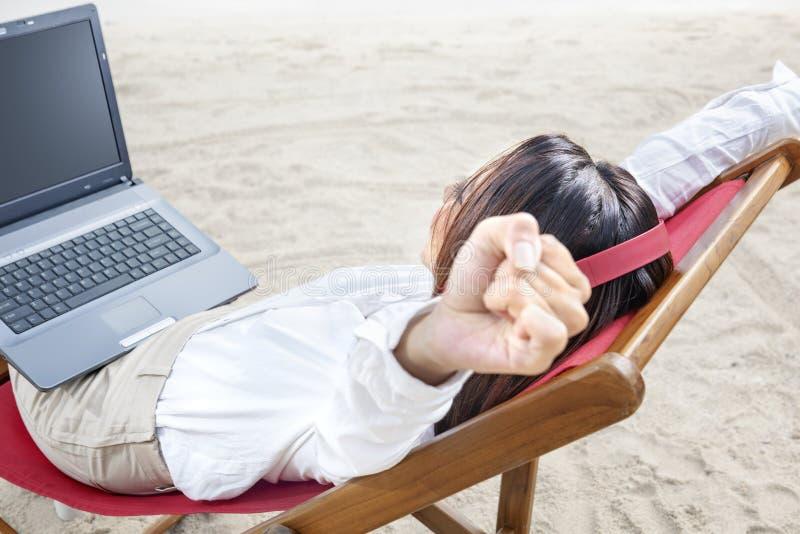 De achtermening van Aziatische bedrijfsvrouw ontspant wanneer het werken met laptop terwijl het gebruiken van hoofdtelefoons zitt stock fotografie