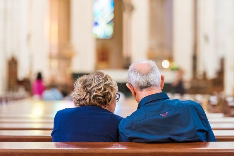 De achtermening van bejaarden koppelt in de kerk, Madrid, Spanje Exemplaarruimte voor tekst stock fotografie