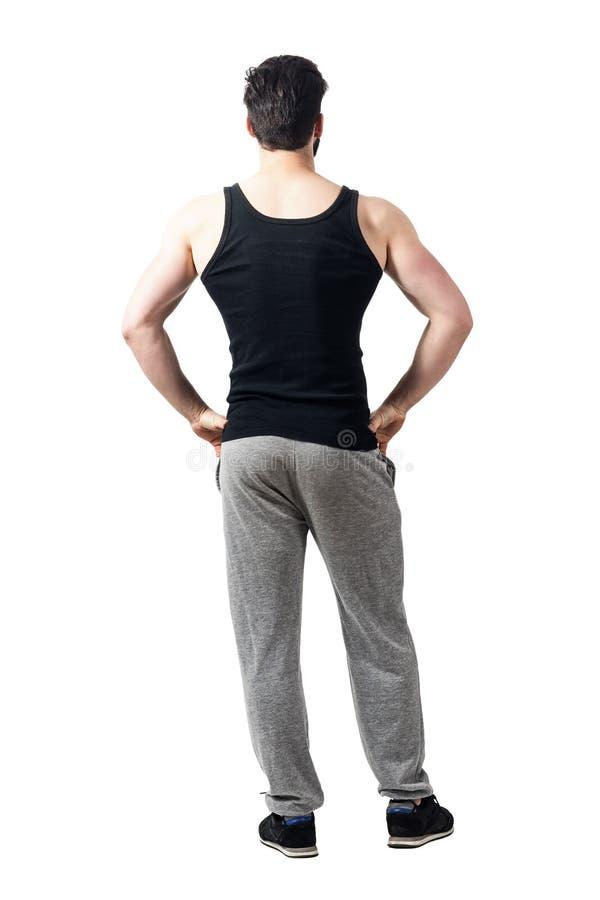 De achtermening van de spiermens die mouwloos onderhemd dragen en jogger hijgt met wapens op heupen royalty-vrije stock foto