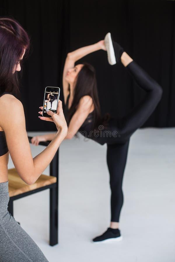 De achtermening van de donkerbruine nemende foto van haar aantrekkelijke atletische meisjesvriend in stelt van bevindende boog in royalty-vrije stock fotografie
